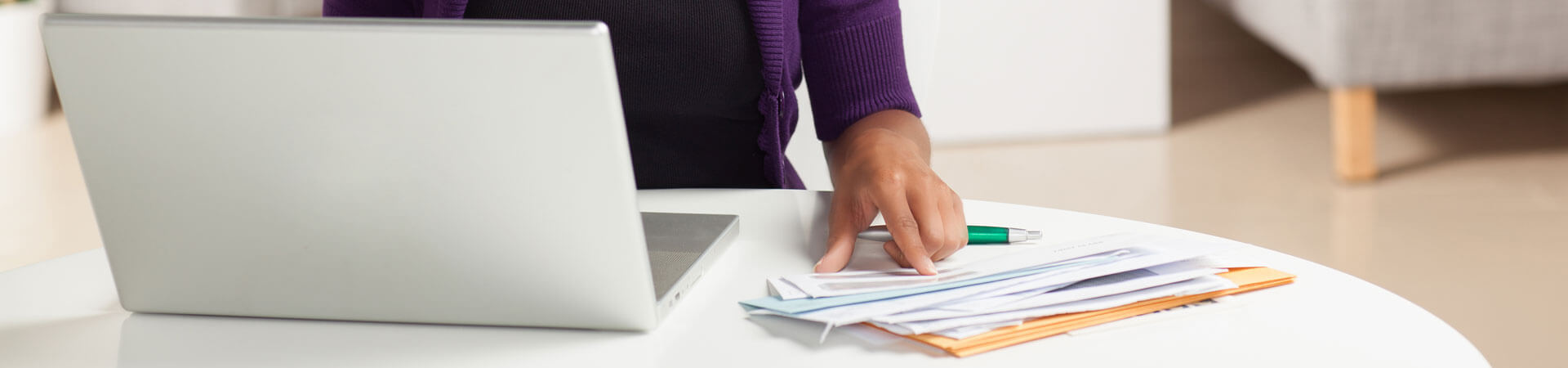 Website banner showing a person using a laptop pointing at some mail on the counter